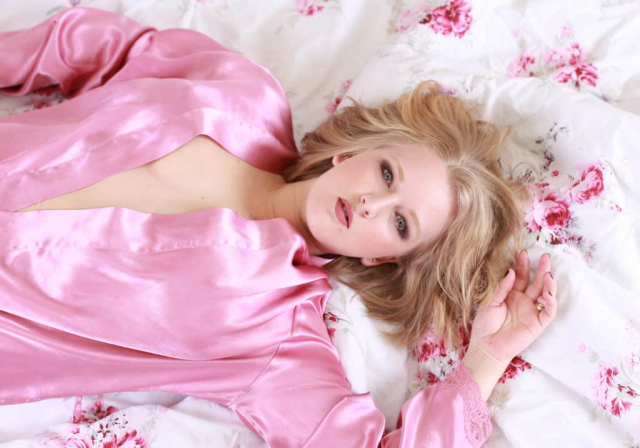 woman in pink silk top laying on sheets boudoir