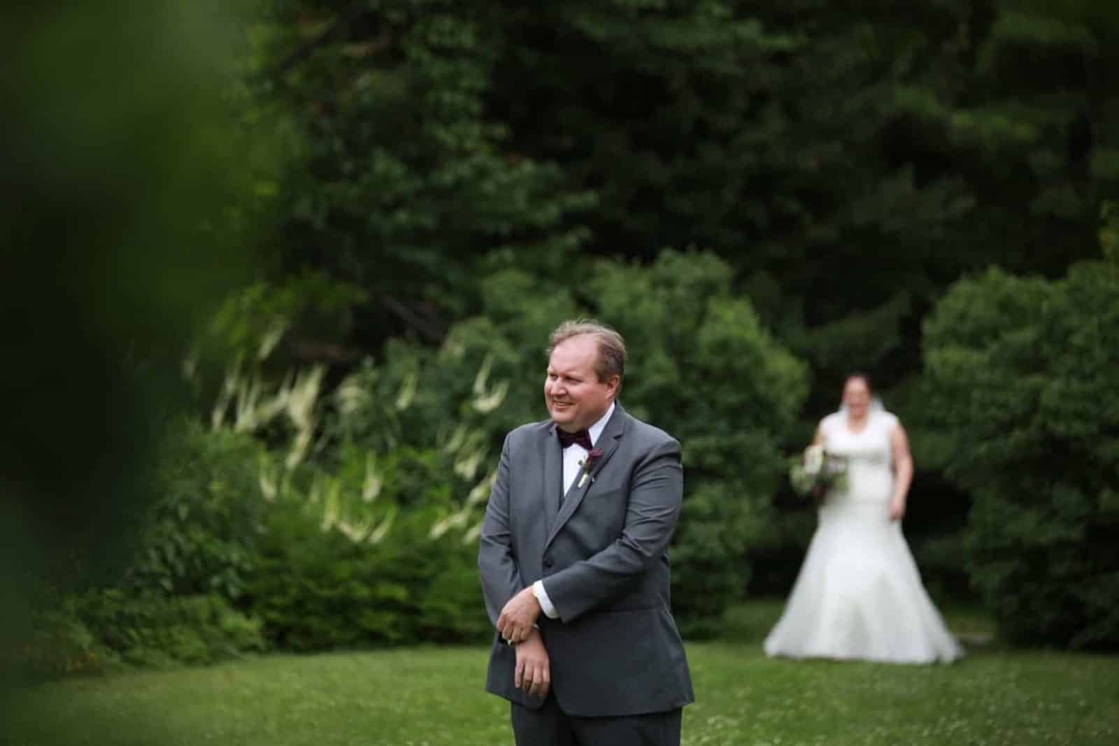 First Look. Groom in focus with a smile bride behind him walking towards grooms back in the ornamental garden