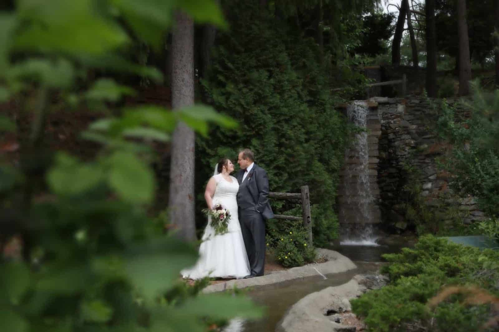 Bride and groom looking at one another near waterfall and stone walk way
