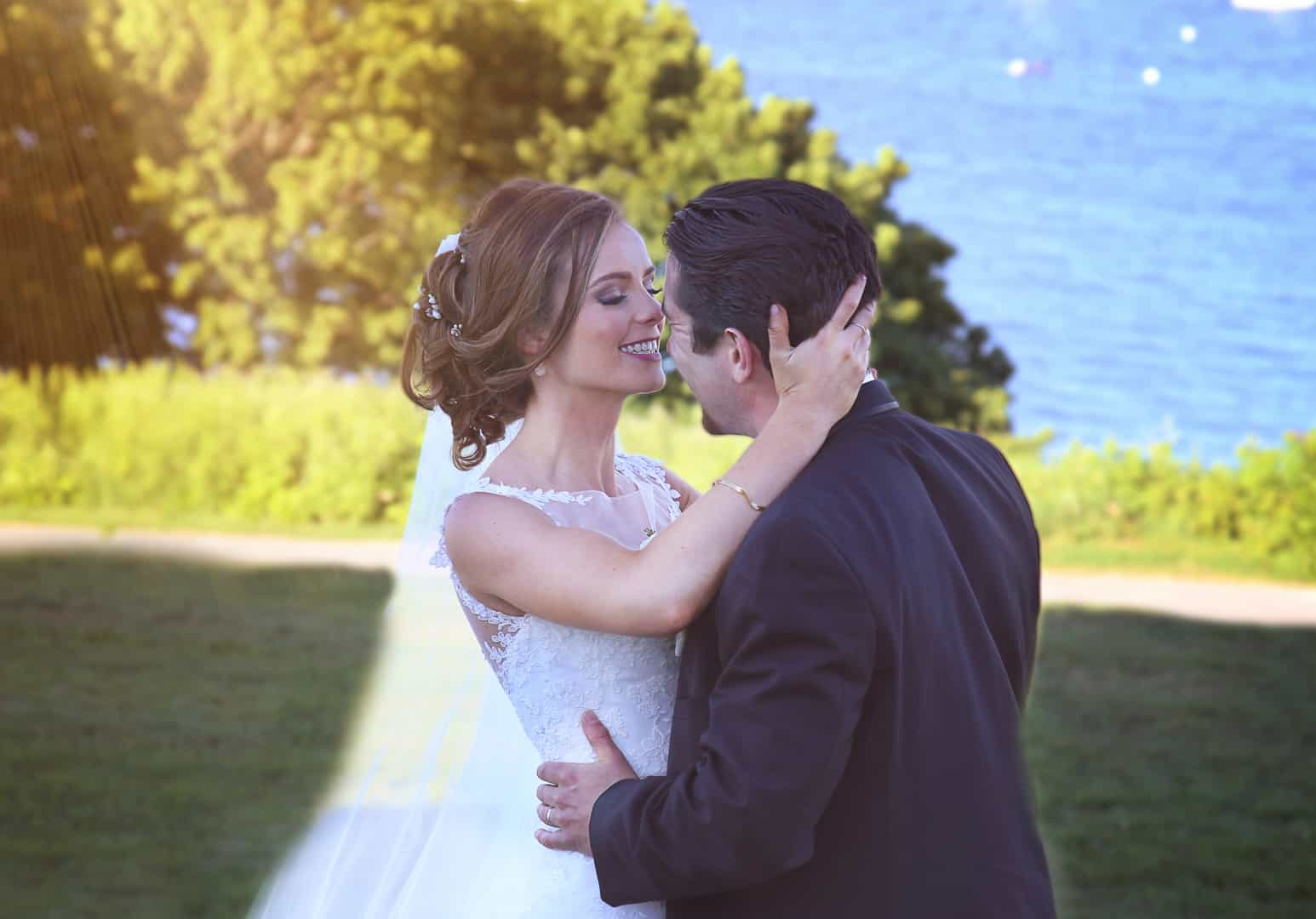 Bride and groom kissing near the ocean with sun beam in the left