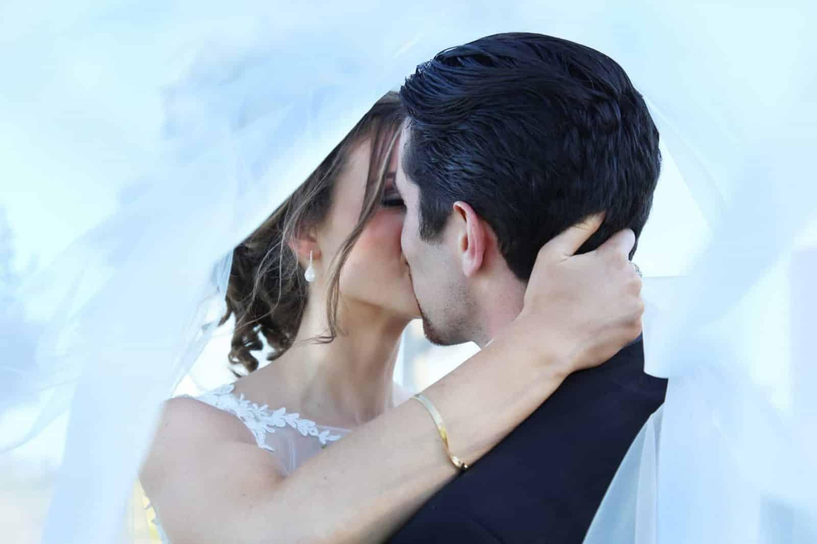 bride and groom kissing under brides vail
