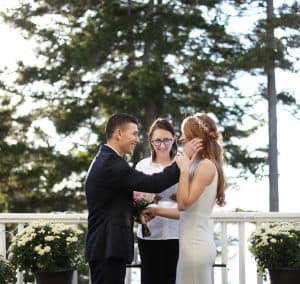 Bride and Groom on the porch getting married overlooking the ocean. Groom kindly touching the brides check