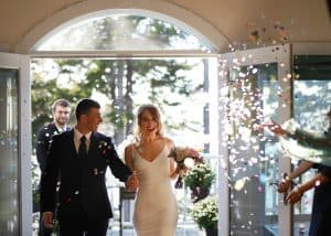 Confetti flying as the bride and groom come in as a newly wed couple