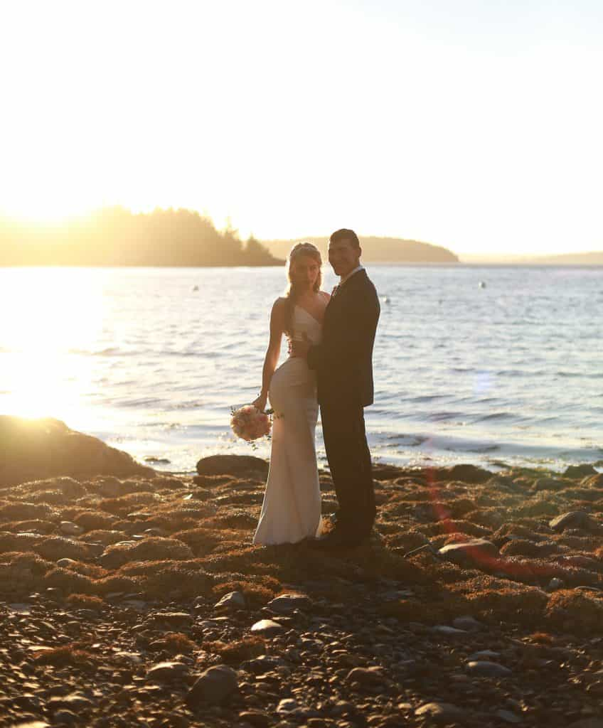 bride and groom at their bar harbor wedding on the ocean at sunset looking at the camera hugging