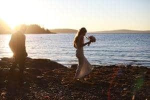 bride and groom walking on the beach, sunset, blue ocean