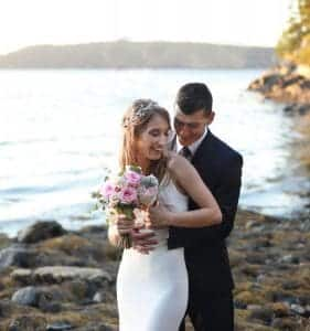 Bride and groom embraced in a hug on the beach overlooking the ocean