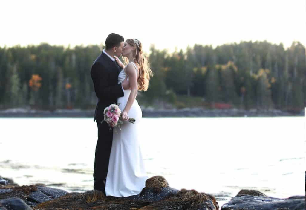 bride and groom getting married in Bar Harbor Maine on the ocean, kissing