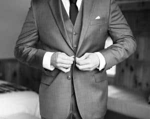 groom doing the buttons on his suit jacket in black and white