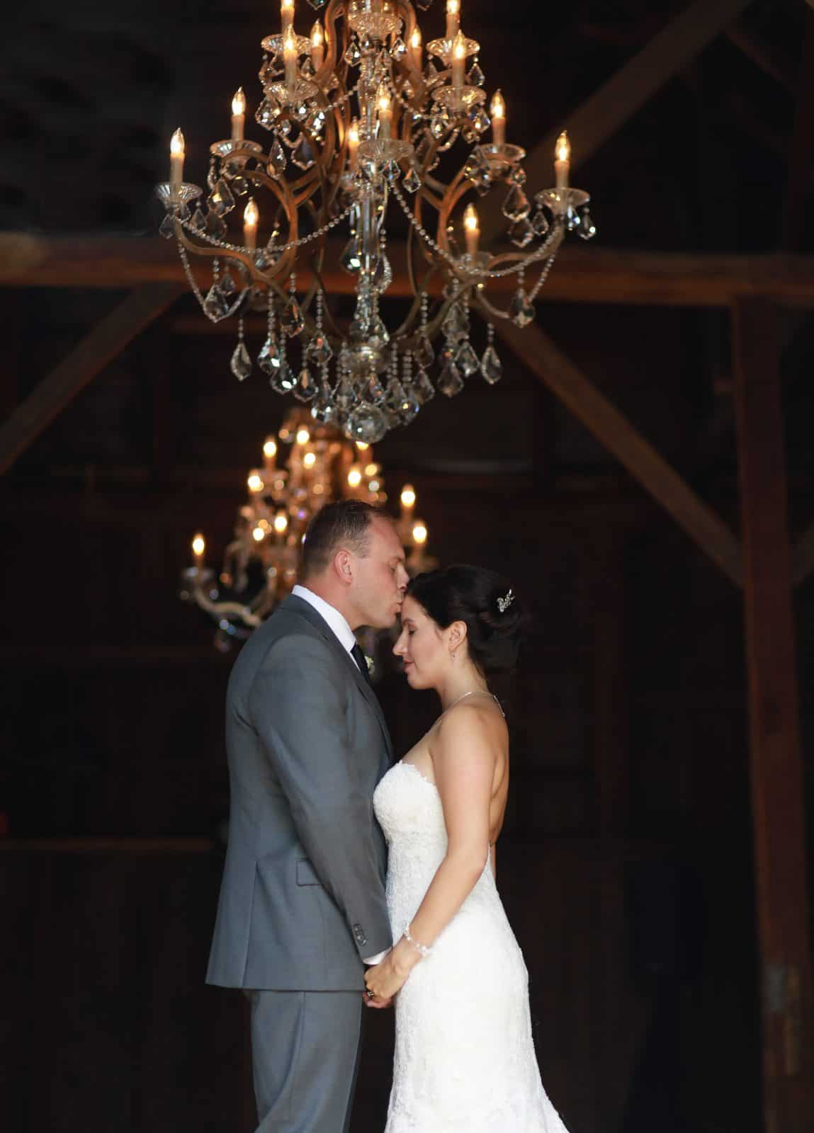 Bride and Groom in a barn with a chandelier embracing one another