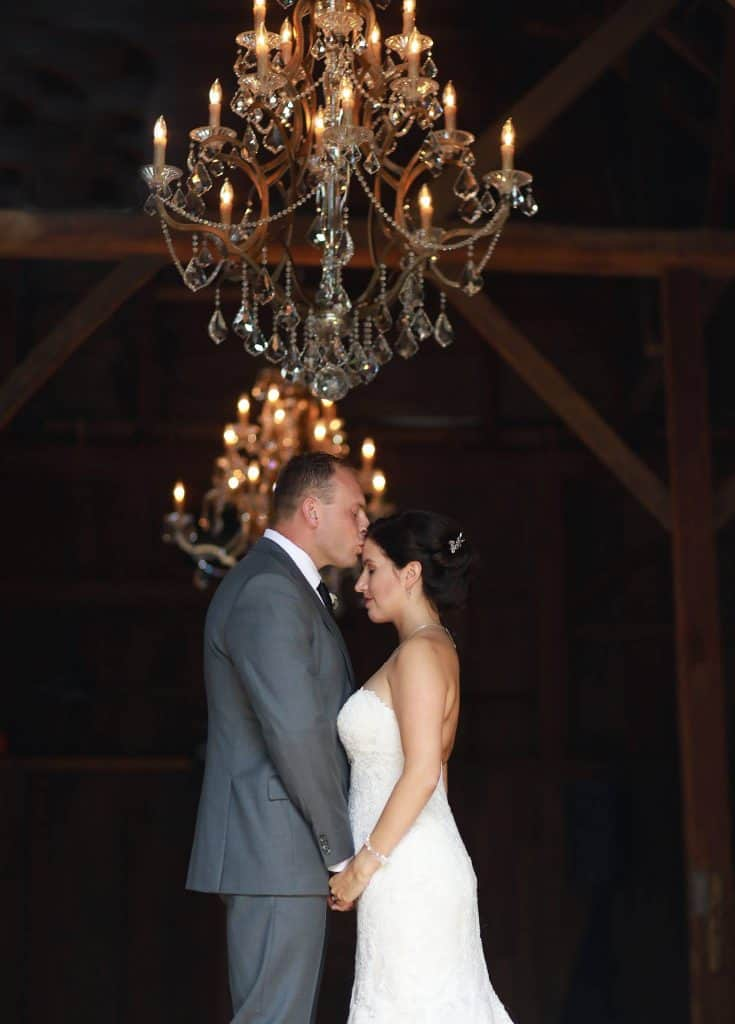 groom kissing brides forhead in barn, chandelier hanging above