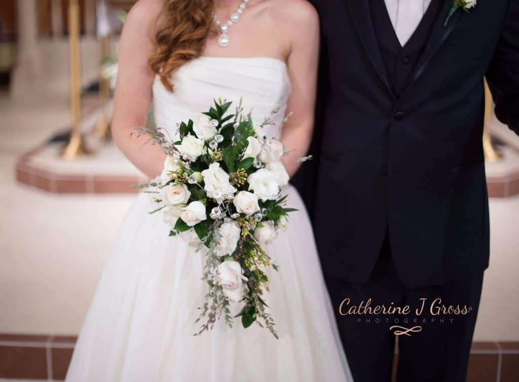 Brie and groom facing camera, picture from the waist down, bride holding wedding bouquet