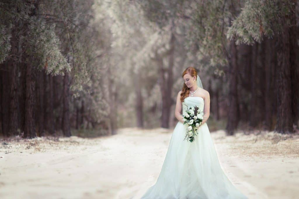 bride in winter wonderland surrounded by trees, holding bouquet looking down her right shoulder