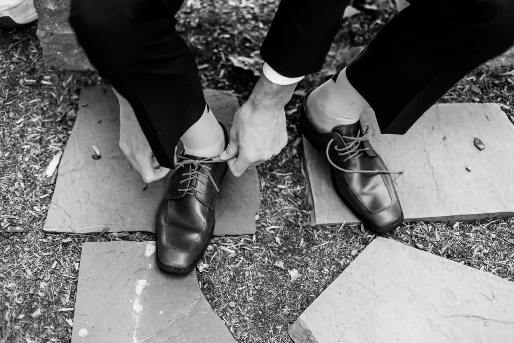 groom tieing his shoes, black and white