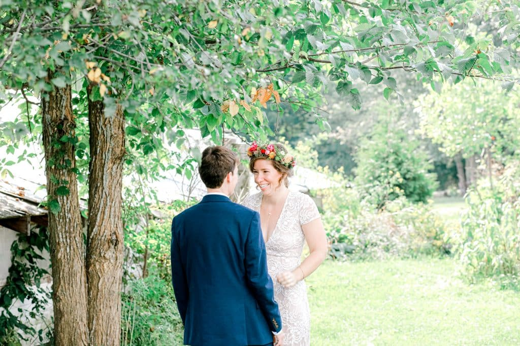 bride and groom first look, bride smiling at her groom under a willow tree