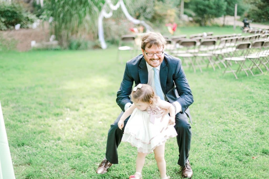 dad and daughter, kids swinging, and guests taking photos of each other
