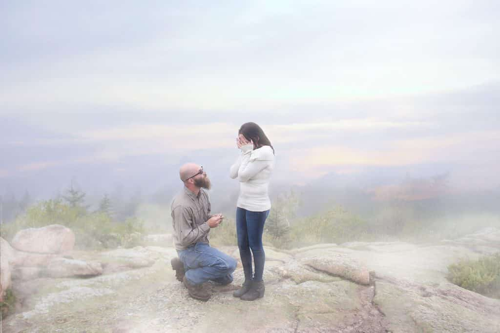 man on one knee proposing to his girlfriend, fog, top of cadillac mountain, maine