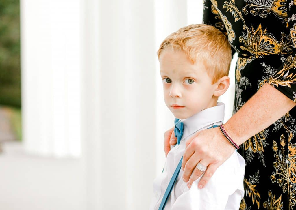 side profile of the ring bearer looking at the camera with his mothers hands on his shoulders