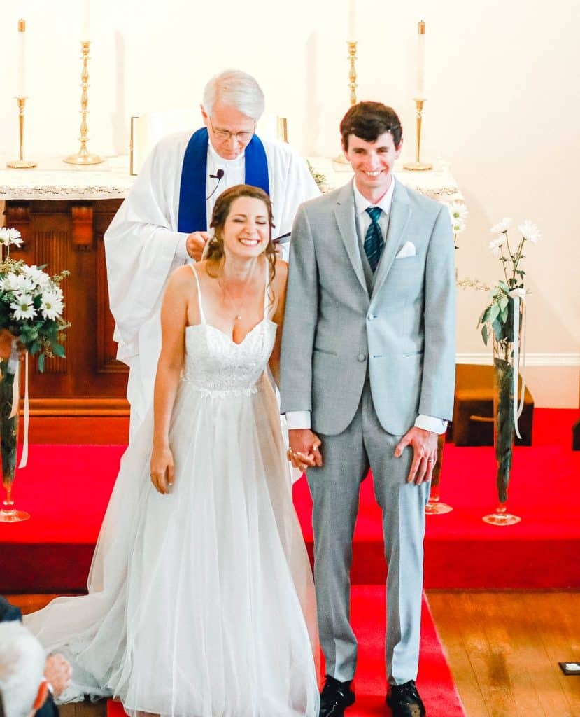 bride and groom looking at the camera, holding hands as a married couple
