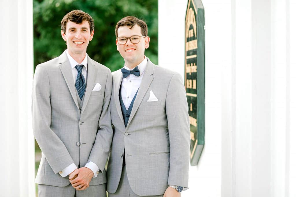 Groom and best man portrait facing the camera with white pillars on both sides