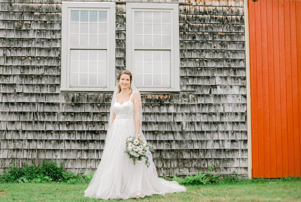 bride portrait looking at the camera with bouquet in front of a barn with a red side