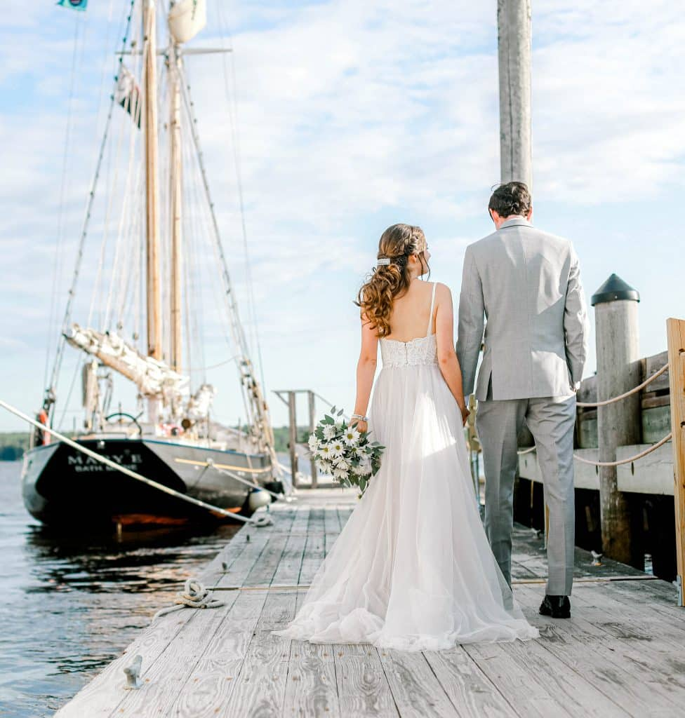 Bride and goom facing away from the camera holding hands, boat to the left of them