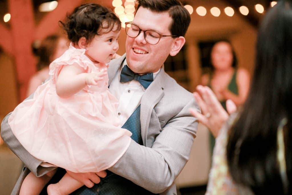 groomsman with dancing with his infanct daughter