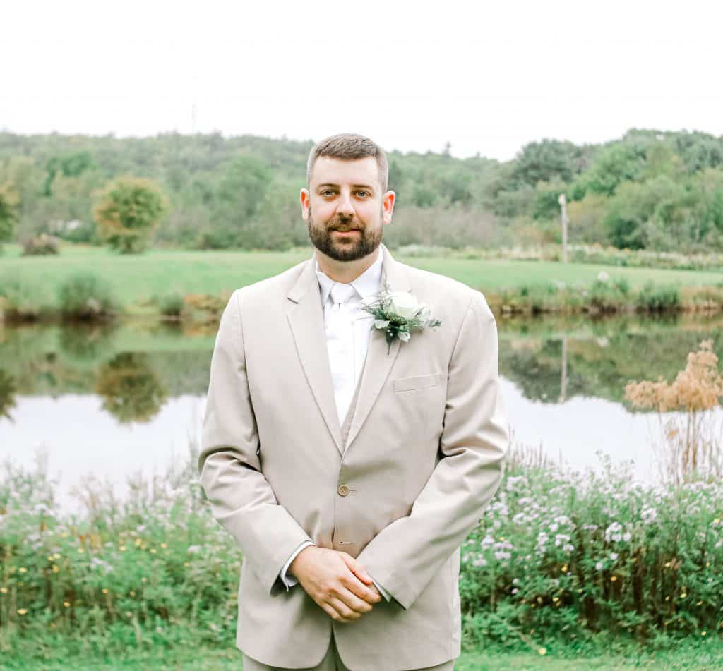 Groom looking at the camera near a lake outside