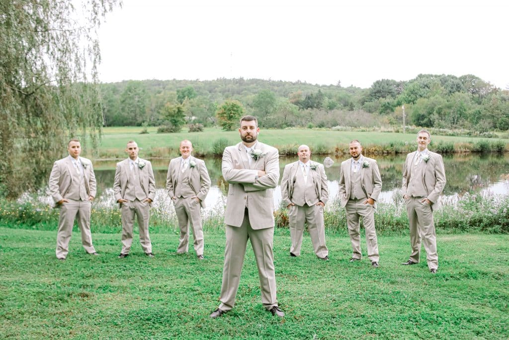 Groom and groomsmen standing near a lake looking at the camera with the groom in front as the main focus