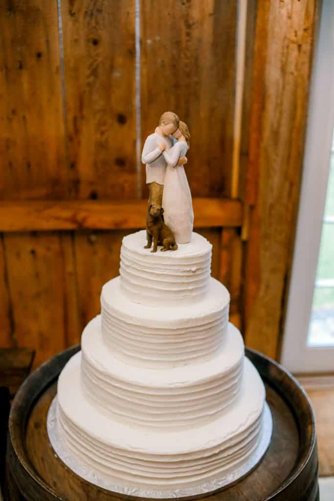 Maine Made wedding cake. White four tear cake with bride and groom figures on top with a rustic wood background
