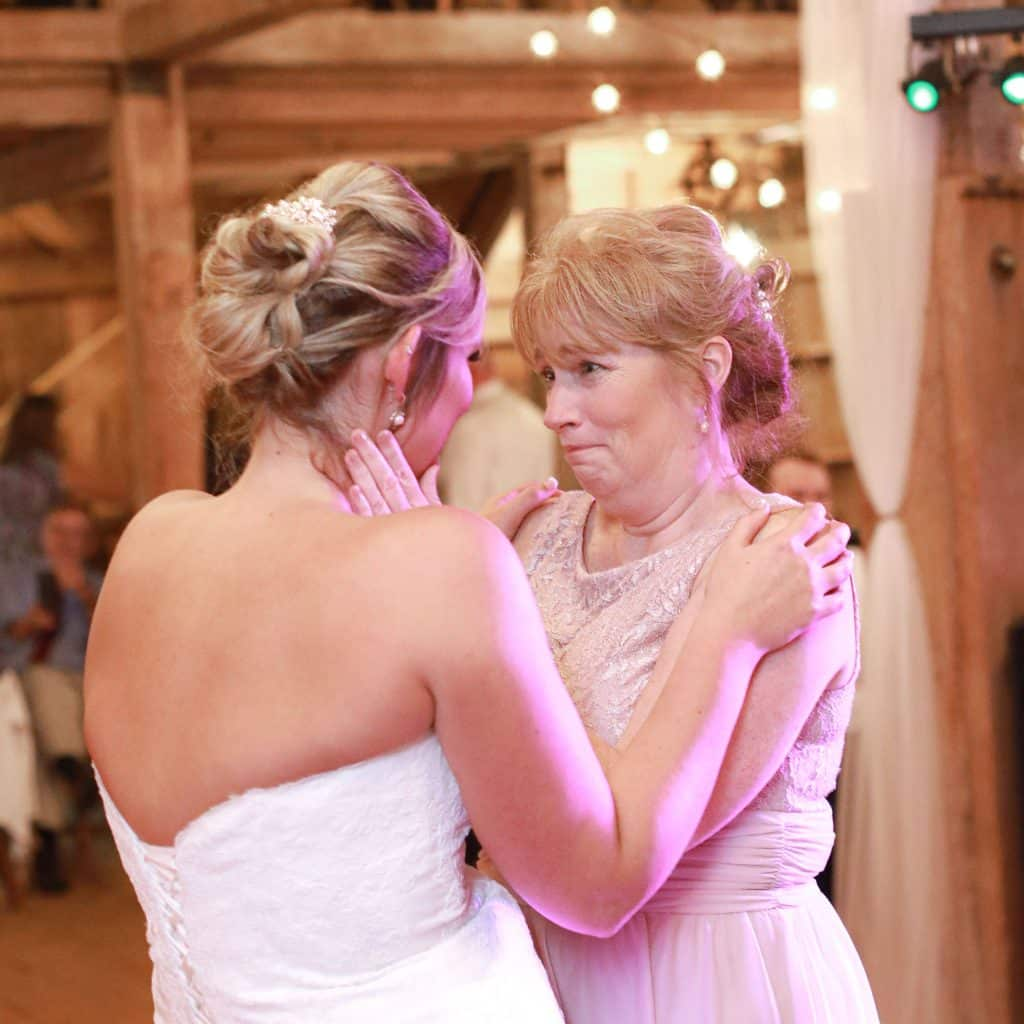 mother crying looking at ehr daughter the bride during their first dance
