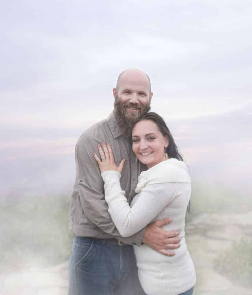 newly engaged couple hugging on top of cadillac mountain, foggy