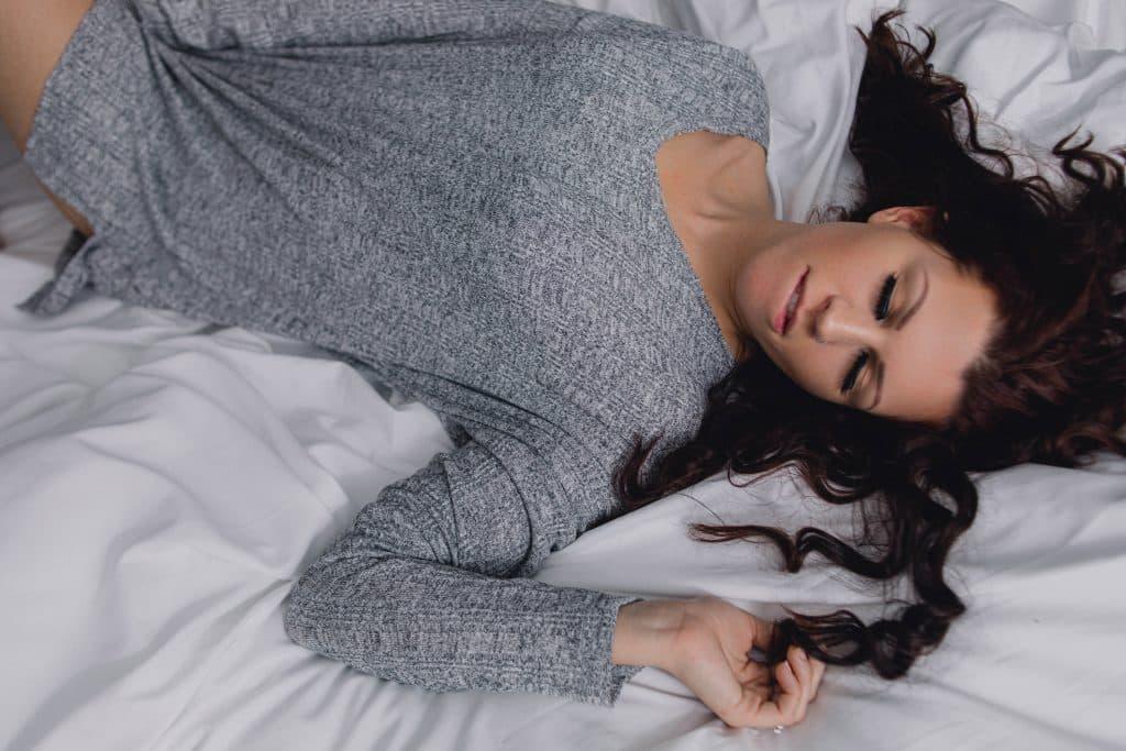 bride laying on white blanket touching hair, eyes closed