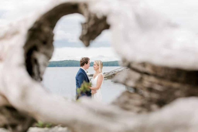 bride and groom through a log