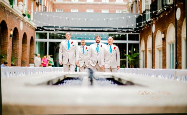 the groomsmen pose over a fountain