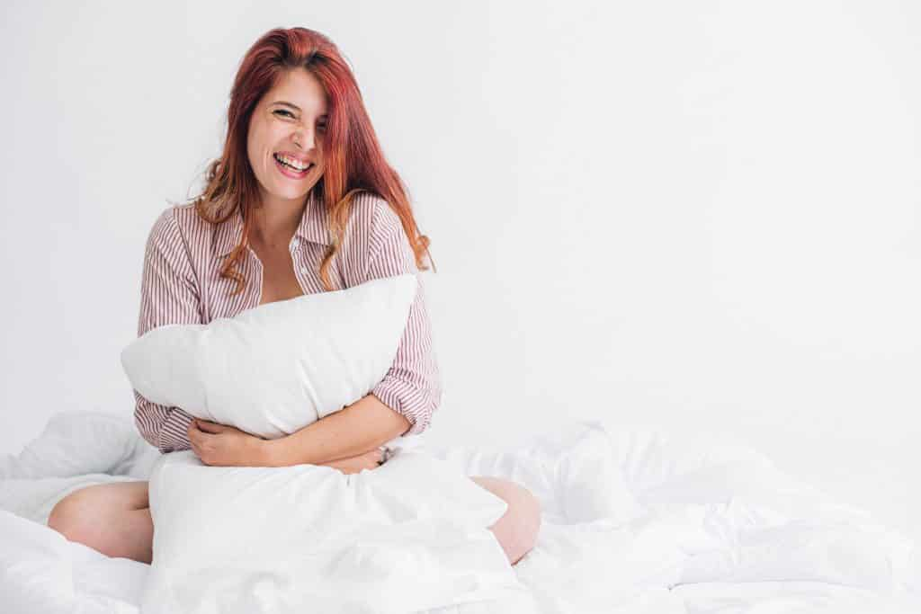 woman in pink t-shirt hugging a pillow in studio