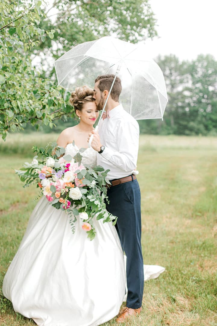 bride and groom holding flower bouquet and clear umbrella