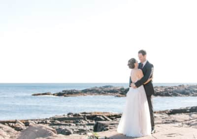 bride and groom on rocky maine beach