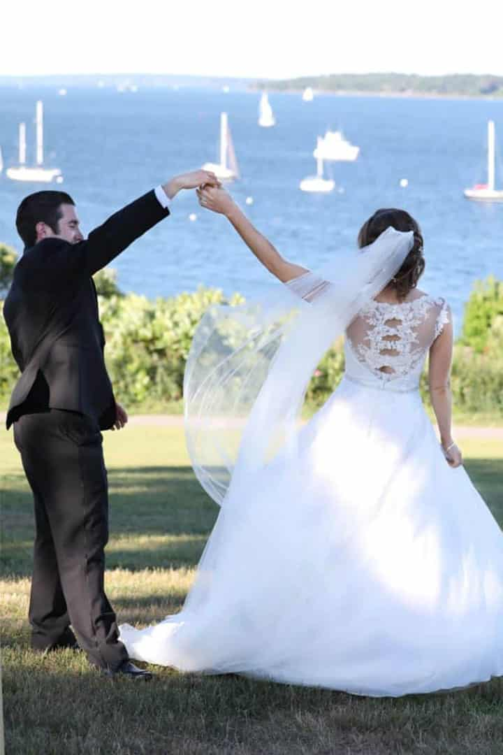 bride and groom on maine ocean with sailboats in background