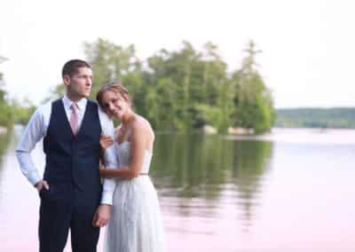 newlywed couple getting a wedding portrait on a maine lake