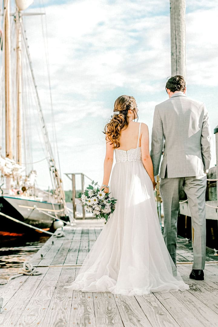 bride and groom walking along a dock next to a sailboat in maine